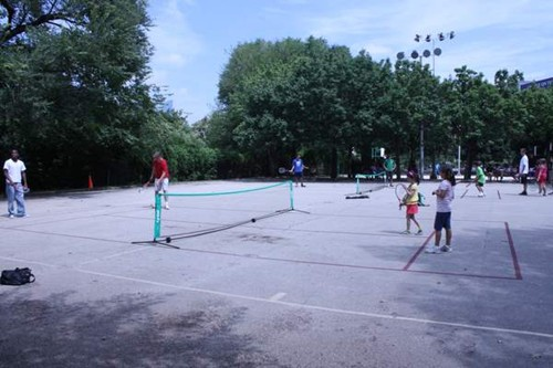 Two 36' tennis courts on a blacktop surface in a public park.